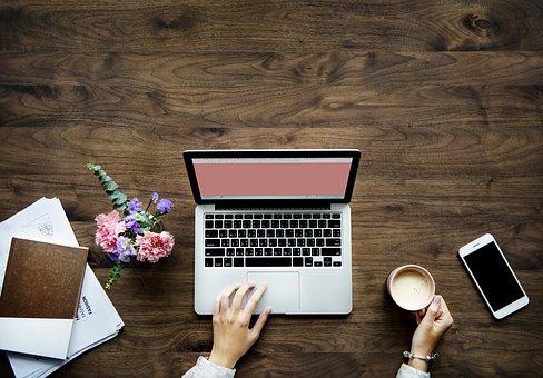 Yrittäjän arkea; Työpöydällä tietokone, kännykkä, työpaperit ja kädessä kahvikuppi.
